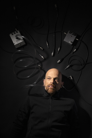 Portrait of Ulrich Troyer in May 2020, with a talkbox and a stompbox, dark atmo, lightspots only on face and effect pedals, photographed by Eva Kelety.