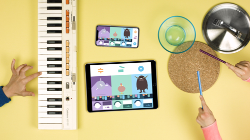 iPad and iphone with BANDIMAL on and 2 Kids playing with a casio organ and a kitchen drums along to the music