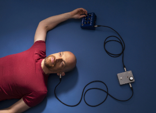Portrait of Ulrich Troyer plugged in with 2 effect pedals in a Stompbox Loop 06-2020 made by Eva Kelety.